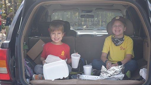 Two kids eating a meal inside of a SUV