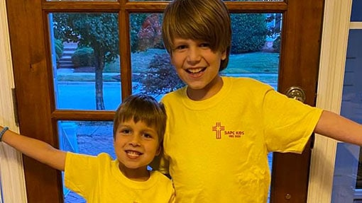 Two boys in yellow t-shirts smiling by a front door