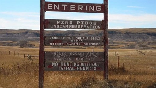 Wooden sign by roadside for Pine Ridge park