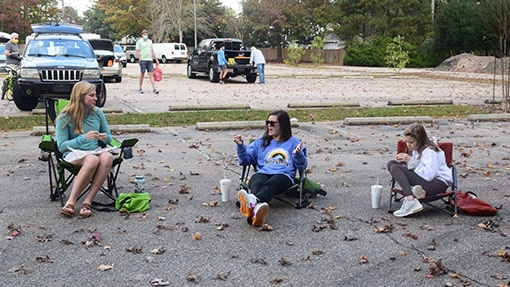 Three high school ladies sharing a meal outside in a parking lot