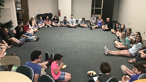 Middle and high school students sitting in a circle for Bible study