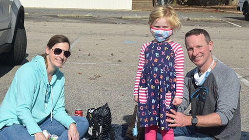 A wife and husband smiling with their daughter in a parking lot