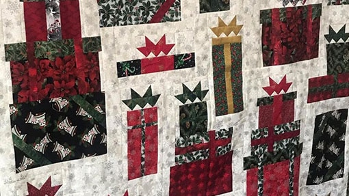 Quilted fabric with a gift box pattern in Christmas colors