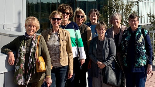 A group of women smiling together outside of a building