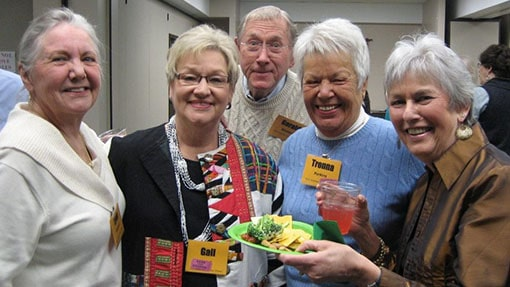 A group of senior adults sharing a meal in a classroom