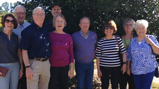 A group of senior adults smiling together underneath a tree