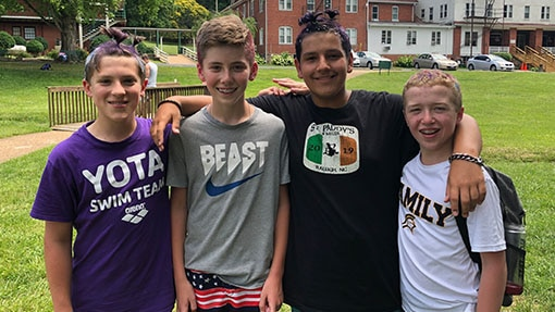 Four middle school boys pose for camera at a summer camp