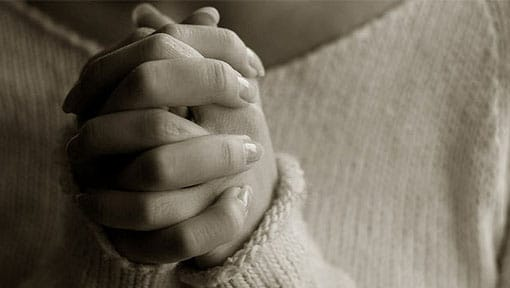 Female hands clasped together in prayer