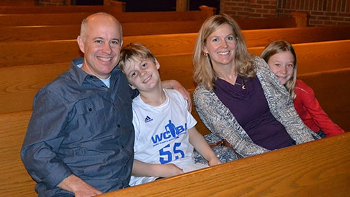A mom, dad, and two boys sitting a wooden pew together