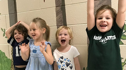 Four girls jumping for joy together in a preschool hallway